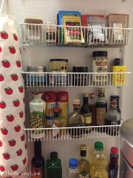 Wire racks mounted to the wall hold spices, vinegar and olive oil