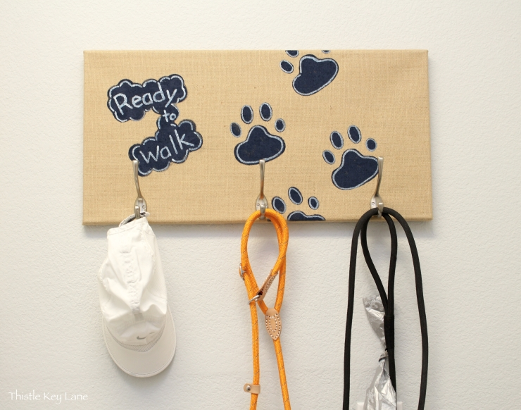 Burlap canvas with hooks for dog leashes.