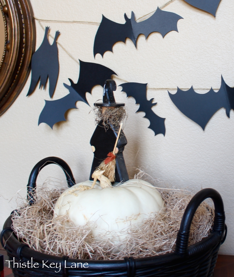 Wooden witch with broom stands on her magic pumpkin