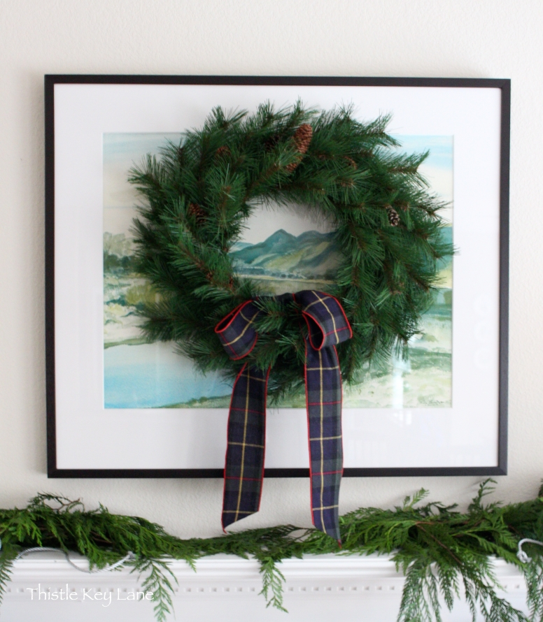 Pine wreath decorated with a plaid ribbon.
