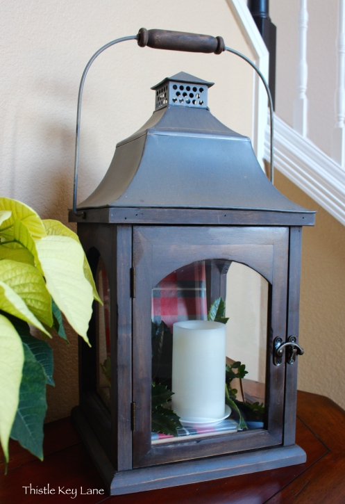 Lantern with plaid covered books, greenery and a candle